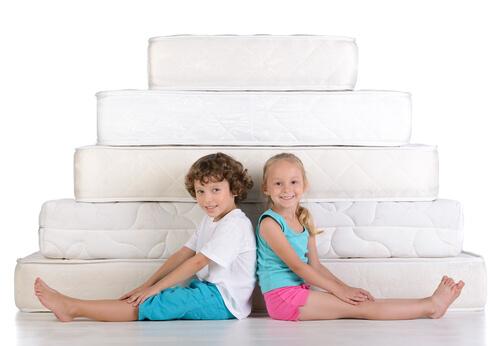 Kinder sitzen vor Matratzen