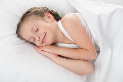 Lächelndes Mädchen liegt auf Matratze
