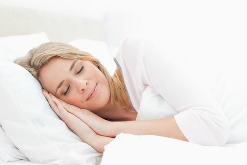 Frau schläft auf Matratze - zufriedener Gesichtsausdruck