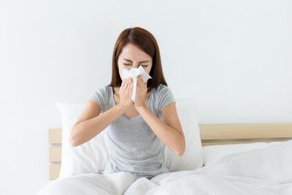 Frau putzt Nase auf Bett