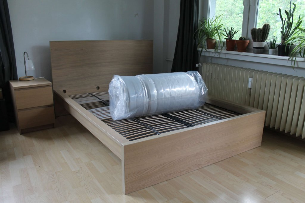 Die eingerollte Matratze liegt auf einem Bett.