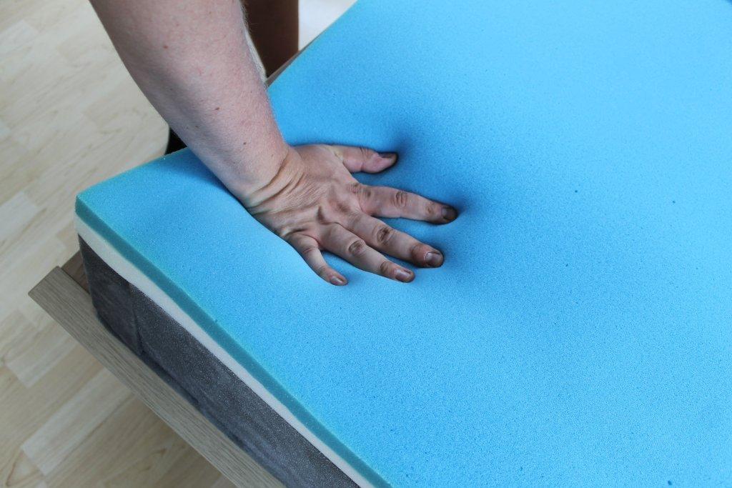Eine Hand drückt den Schaum nach unten.